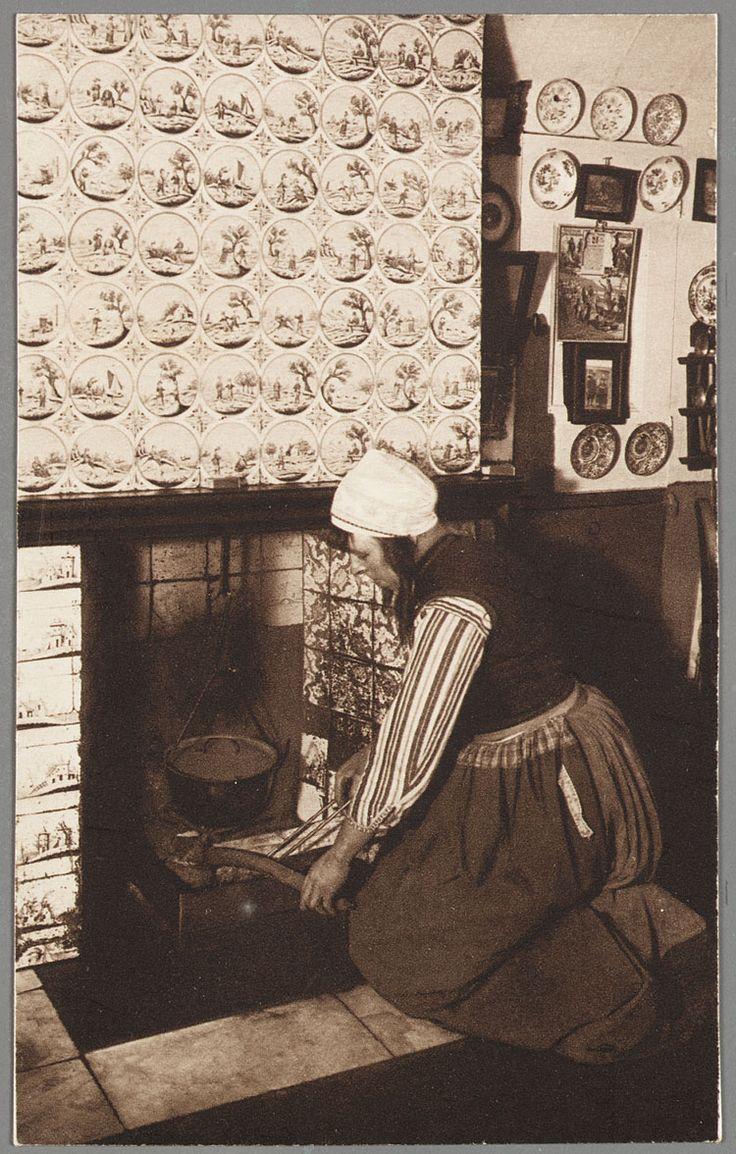 Vrouw in Marker klederdracht stookt het vuur op bij een betegelde schoorsteenmantel. 1910-1920 #NoordHolland #Marken