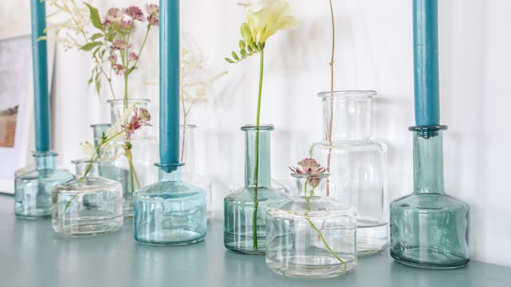 Haal het voorjaar in huis met kleine vaasjes gevuld met kaarsen en bloemen.