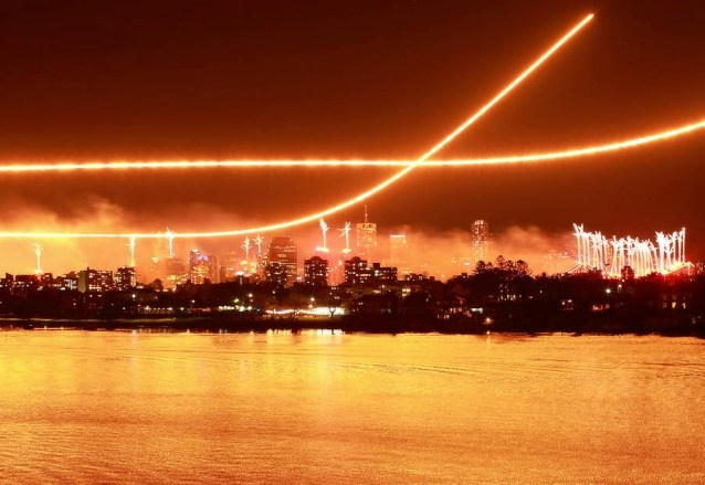 Wow! A city apparently on fire at Riverfire 2009; Brisbane lit up by the fireworks and intersecting dump-and-burns of two F-111s, painting the river a flaming orange hue.