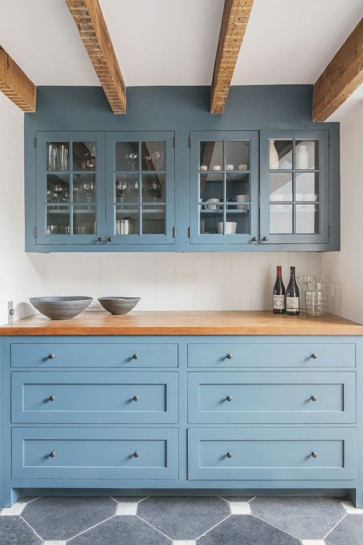 Bright open kitchen with light blue cabinets, butcher block countertops, exposed beams and glass front cabinets.