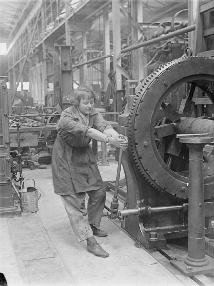 INDUSTRY DURING THE FIRST WORLD WAR: WOOLWICH ARSENAL © IWM (Q 27839)  A female worker operates a naval gun rifling machine in the Royal Gun Factory at the Royal Arsenal, Woolwich, London, in May 1918.