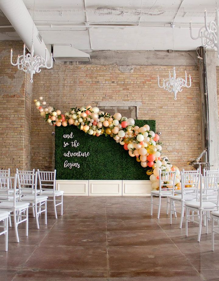 Balloon Installations As Wedding Decor ~ Balloons and greens garland attached to ceremony backdrop by Girl Friday