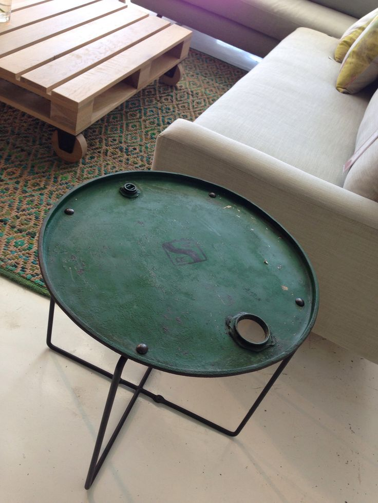 Drum head with wire legs, turned into an end table (note pallet or constructed pallet icon in the middle with casters on).  Edgy.