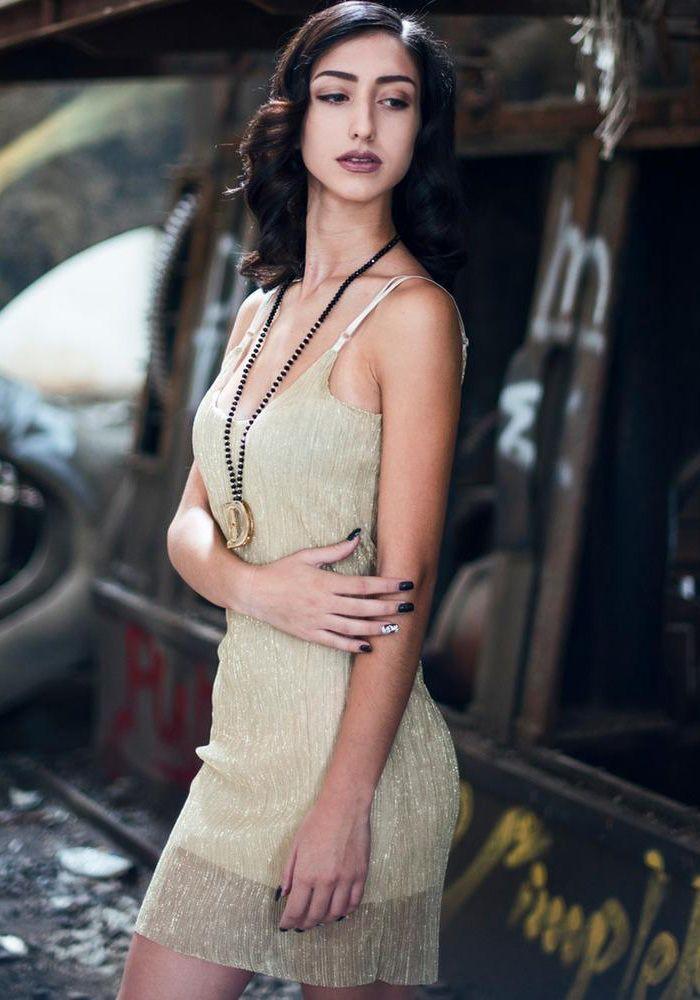 Φόρεμα mini με ραντάκι και ντεκολτέ. Είναι μεταλιζέ πλισέ με ενσωματωμένο ύφασμα καιανοιχτή πλάτη. Είναι ένα trendy φόρεμα που μπορεί να φορεθεί με ψηλό η χαμηλό παπούτσι. Συνδυάζεται ανάλογα με την περίπτωση με τζιν μπουφάν η με ένα καλό πανωφόρι.  VISCOSE 95% - ELASTHAN 5%