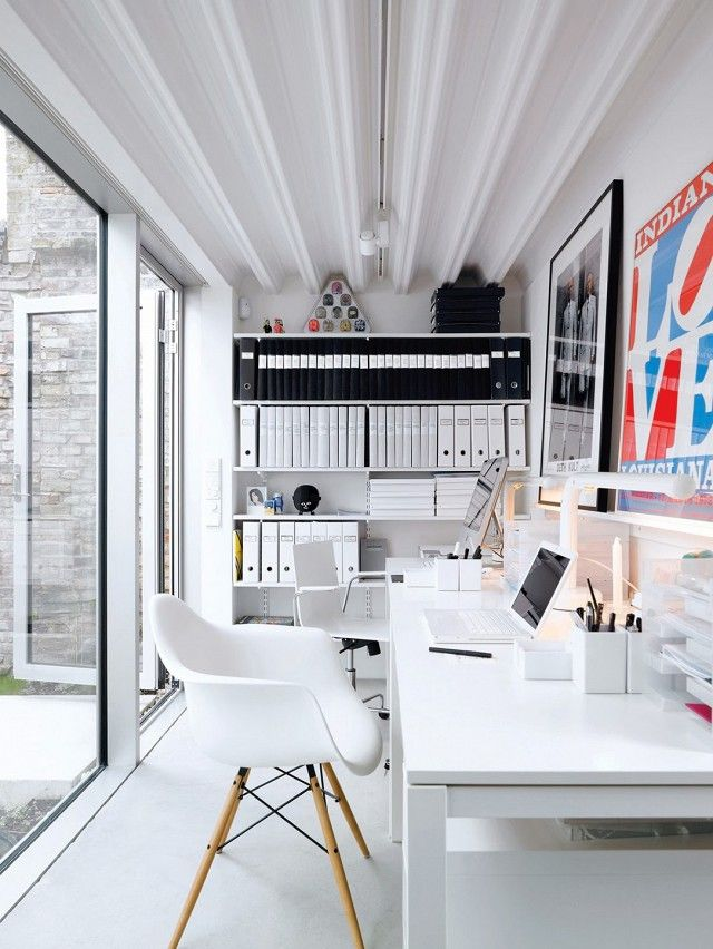 Bright organized office space with modern white chairs and eclectic art