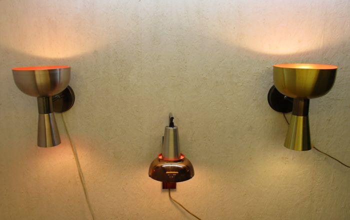 """O.a. Hema -Drie Space Age wandlampen  Drie wandlampen uit de jaren zestig  uitgevoerd in aluminium .Alle drie met een oranje kleurige binnenkant.Twee lampen met dubbele fitting het licht straalt dus zowel naar boven als naar beneden zie foto's.De lampen hebben dezelfde vorm maar 1 lamp is zilverkleurig en de andere lamp goudkleurig.Gemerkt : ja de goudkleurige lamp is gemerkt met sticker """" HEMA """"  zie foto's. De derde lamp met houten wandconsole heeft 1 fitting. De kap is…"""
