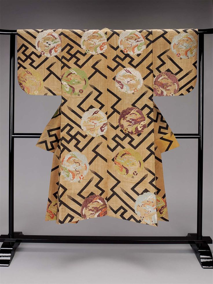 Noh theater robe (atsuita), for male role, with a light tan twill-weave silk ground and an overall design of blue-black interlocking swastika pattern (manji tsunagi) and dragon (ryu) roundels in purple, light blue, green, yellow-green, reddish-orange and white silk and gilt paper discontinuous supplementary patterning wefts; reddish-orange plain-weave silk lining.