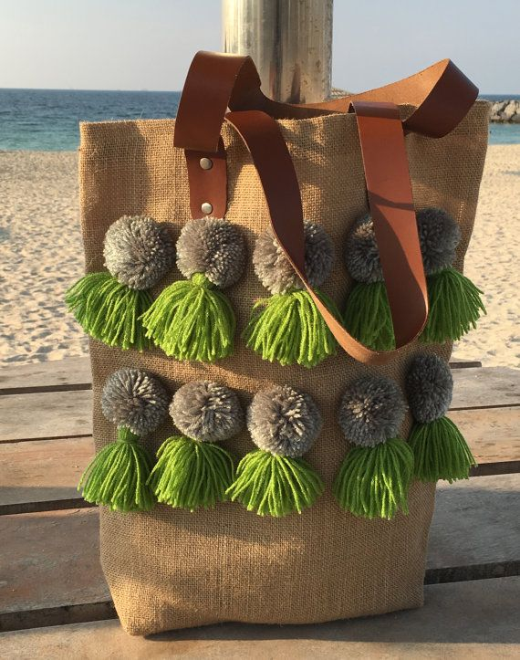 This boho tote bag is made from jute burlap and is adorned with wool pom poms in grey color with wool tassels in green color. Its a perky