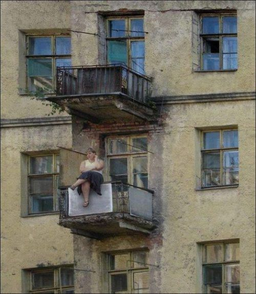 Lady sat on a decaying balcony, precariously balanced!