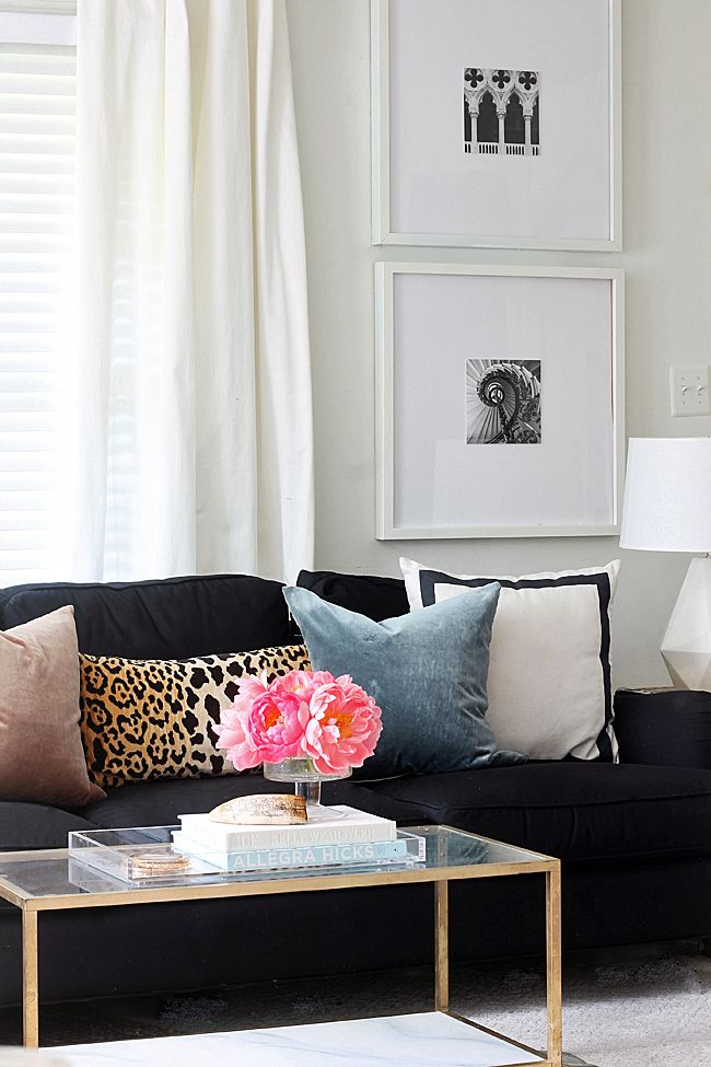White window coverings white walls black sofa and colourful cushions