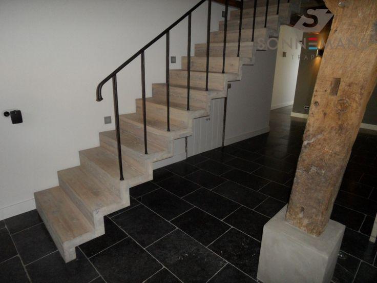 Eiken houten blok trap met een smeedwerk hekwerk. Deze trap staat vrij van de muur.