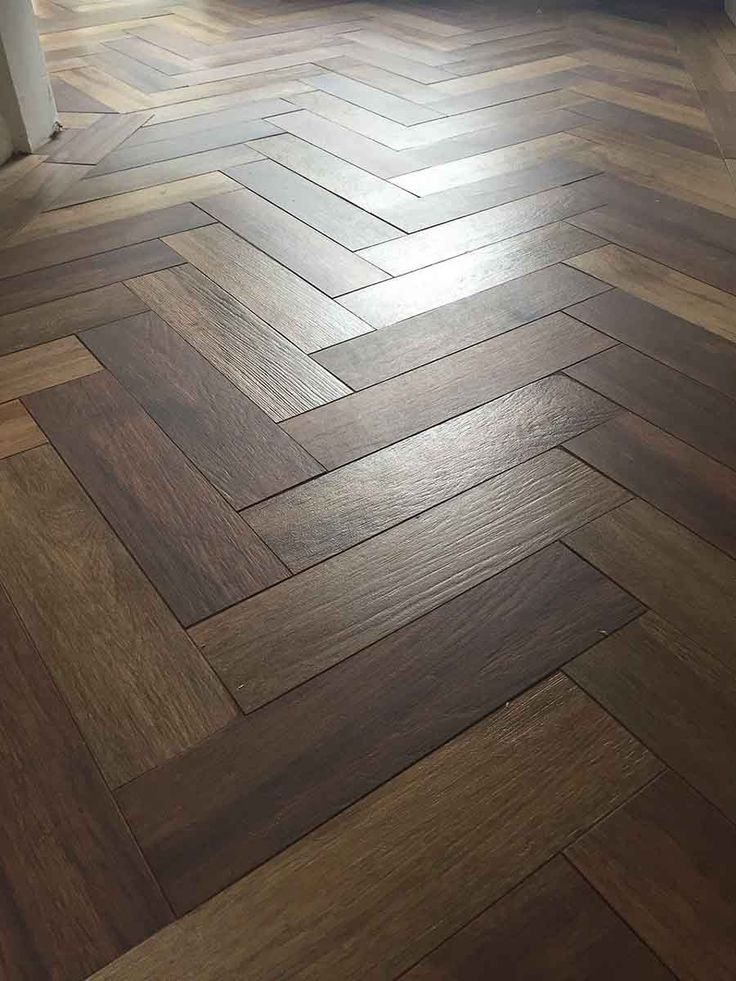 Dark wood effect porcelain floor tiles laid in a herringbone pattern