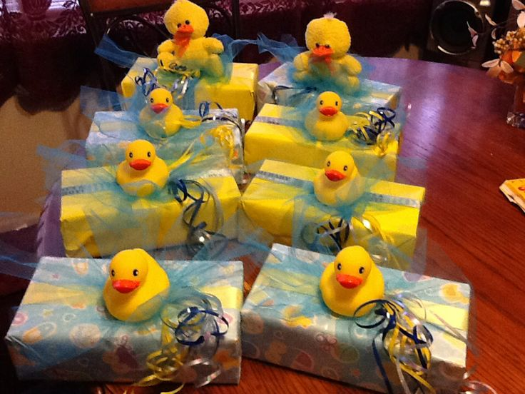 Handmade table decorations for baby shower. Glove box with wrapping paper, ribbon, plastic ducks and glue gun