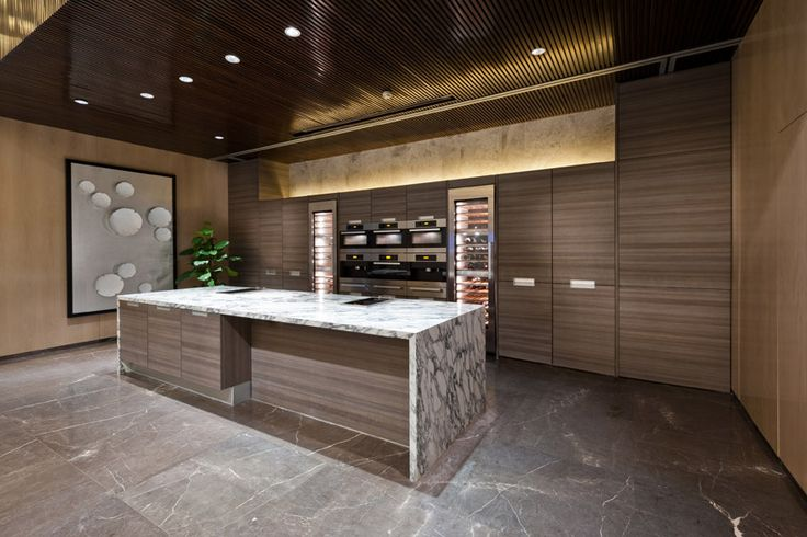 Modern wood kitchen with rectangular island and a marble countertop.