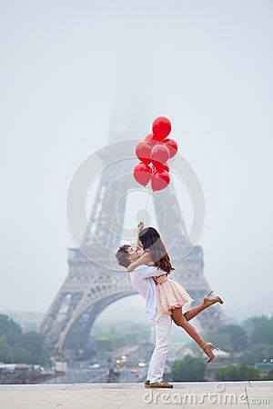 Romantiska par med röda ballonger tillsammans i Paris