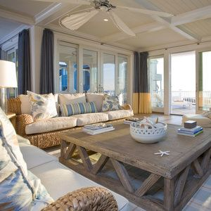 In this gathering space, an oversize coffee table anchors the space and suits its large size; architectural detailing like coffers and a tongue-and-groove ceiling warm up the voluminous room. Framing the glass doors are colorblock draperies; the blue sign