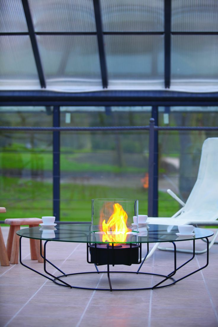 Fire Coffee. Stolik kawowy zaprojektowany przez Arika to model o szerokiej podstawie wykonanej z metalowych elementów kształtem przypominających rozetę. Szklana pokrywa spoczywająca na rozecie sprawia, że jest to nieprzeciętny stolik. Unikatowość uzyskana jest dzięki szklanemu cylindrowi, w którym żywe płomienie tańczą nie wydzielając dymu. Jest doskonałym uzupełnieniem przestrzeni zewnętrznych i wewnętrznych, ponieważ nie wymaga instalacji kominowej.