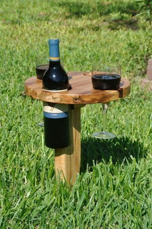 """Park picnic wine table: It folds up and has a built in handle for carrying.  Insert the pointed peg into the ground. Fold the table top over on its wooden hinge. Then, enjoy a nice bottle of wine without concern of where to set your wine bottle or tipping over your glasses. This solid oak table is 12"""" in diameter and has more than enough room for light snacks! by PennyTaylor"""