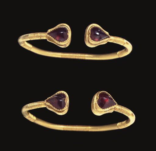 A PAIR OF GREEK GOLD AND GARNET BRACELETS   CIRCA 1ST CENTURY B.C.   The solid-cast penannular hoops round in section, four sets of ribbed bands along the length, terminating in two heart-shaped garnets, the bezels with scalloped borders