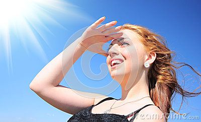 Beautiful young woman smiling in the sun against blue sky