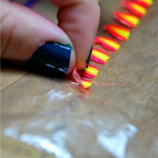 Paint a nail design onto a zip lock bag, let dry, peal off, put on finger nails paint over with clear or top coat.  All done!