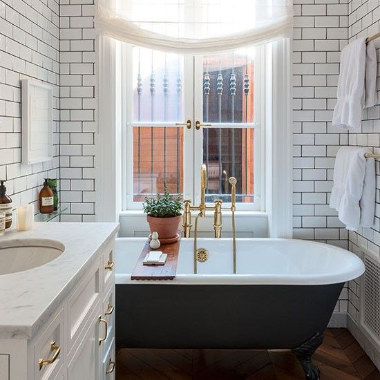 Floor-to-ceiling tiles emphasise the height of this bathroom, while the monochrome colour scheme gives it a sense of serenity.