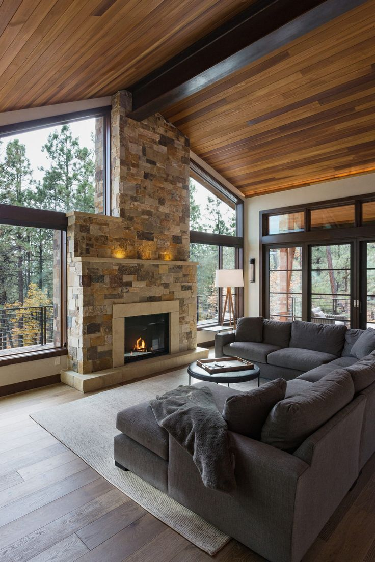 Kogan Builders designed this Modern living room with amazing floor to ceiling windows, a gorgeous wood ceiling and a stunning stone fireplace in this mountain contemporary home in Durango, CO