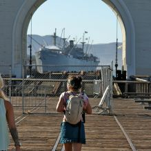 """""""Don't know if I'm about to catch that boat. Take off the fences so I can run and jump"""". Pedestrian and a boat seen through an arch on Embarcadero, San Francisco. © Miikka Järvinen 2013"""