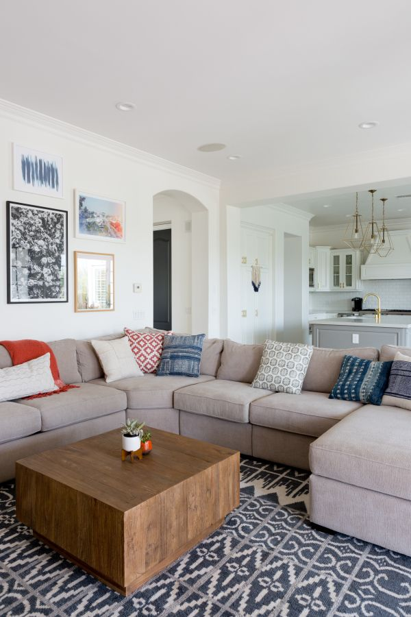 Taupe family room sectional couch and wooden coffee table: http://www.stylemepretty.com/living/2016/09/16/see-how-a-party-stylist-translates-her-cool-girl-style-into-her-home-x2/ Photography: Amy Bartlam - http://www.amybartlam.com/