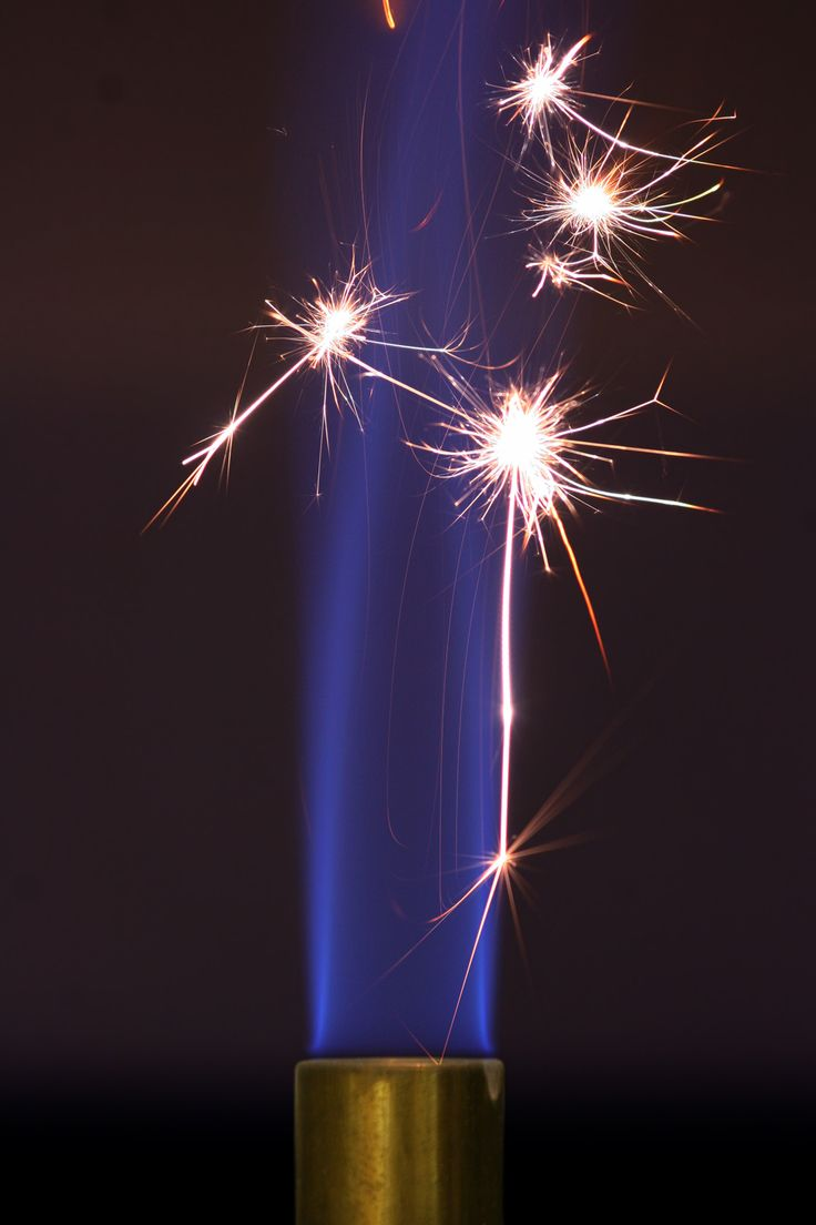 Activation energy is the energy that must be overcome for a chemical reaction to occur. Here, the sparks generated by striking steel against a flint provide the activation energy to initiate combustion in a Bunsen burner. The blue flame will sustain itself after the sparks are extinguished because the continued combustion of the flame is now energetically favorable.