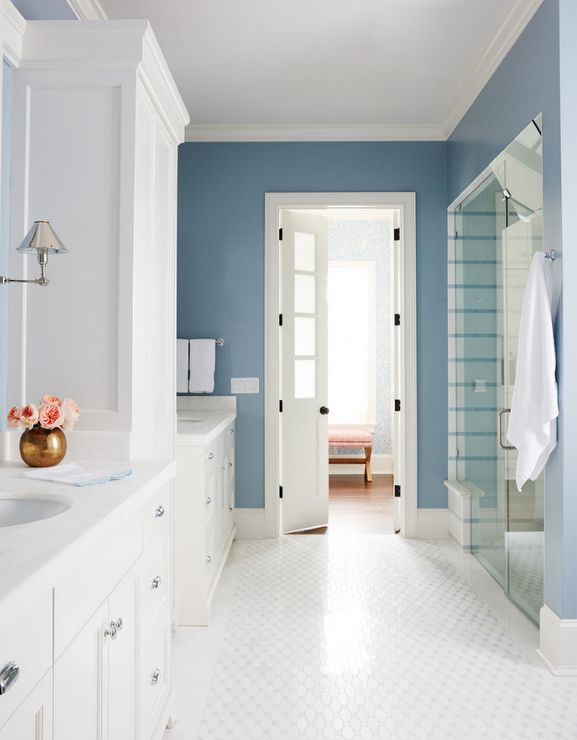 White and blue bathroom features white his and her washstands illuminated by Anette Single Sconces, separated by a tall cabinet, alongside a white geometric tiled floor.