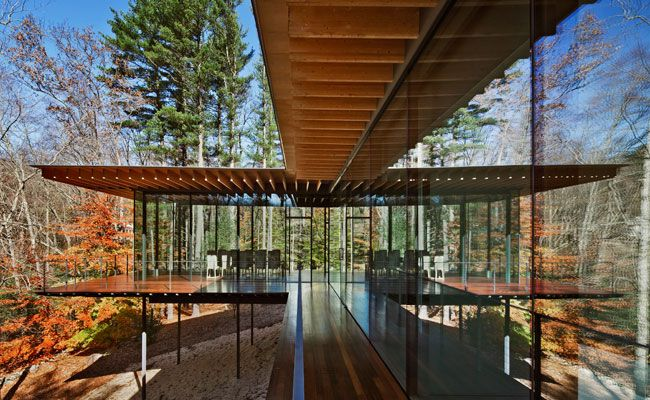 The roof of Kengo Kuma's addition to an American mid-century Modern house cantilevers from columns pulled behind its all-glass skin.