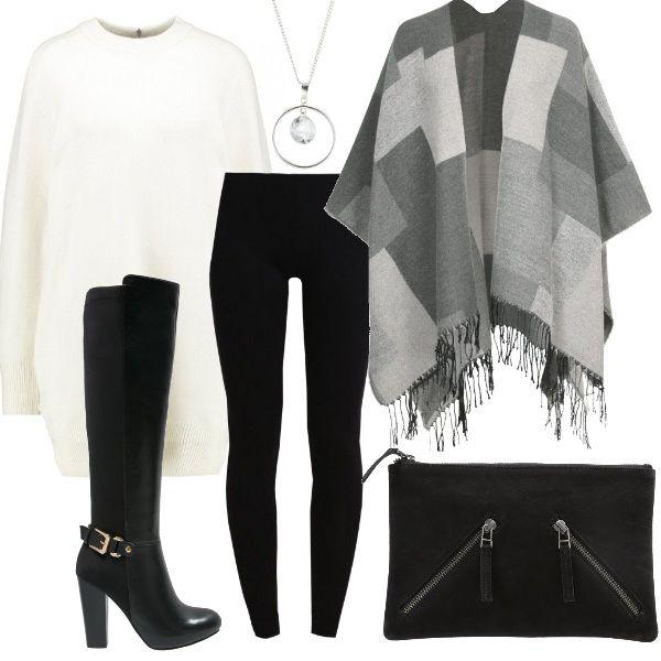 Outfit formato da maxi pull bianco indossato con leggings e stivali a tacco alto, per mettere in evidenza le gambe anche in pieno inverno. Mantella con frange sui toni del grigio e pochette con cerniere, nera.