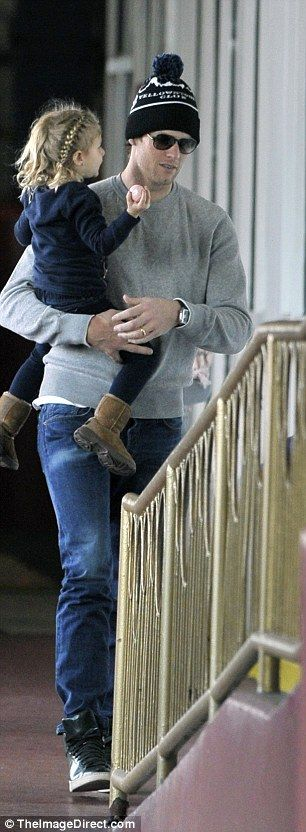 Stylish: Gisele wrapped herself in a black sweater while Tom carried Vivian up the steps...