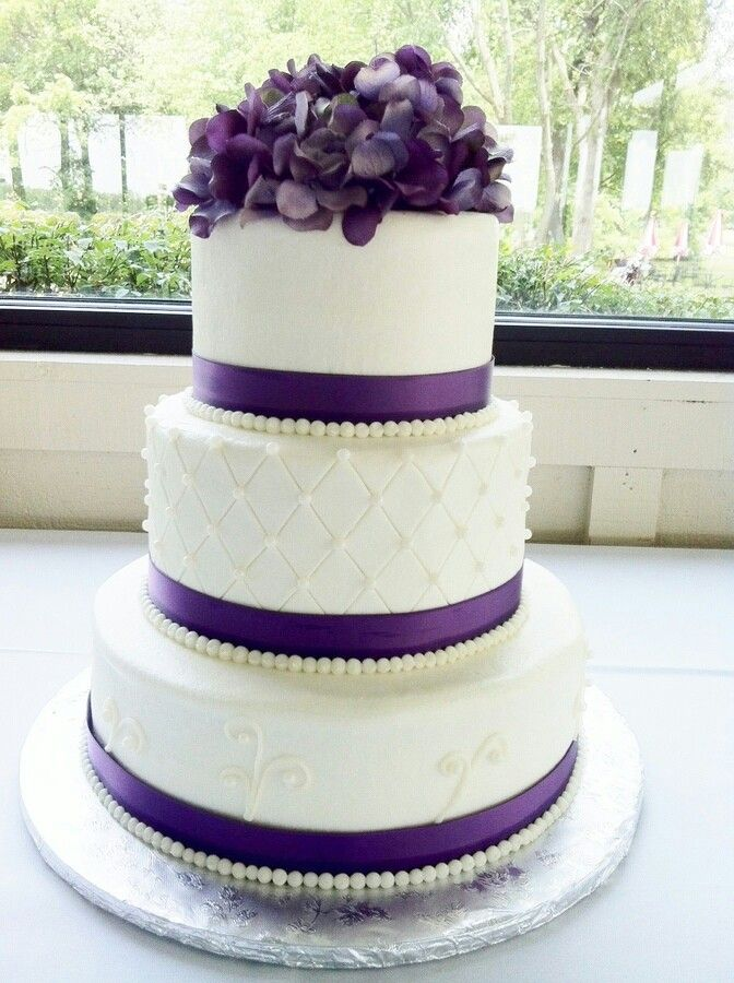 Elegant white and purple cake with flowers and ribbon to boot