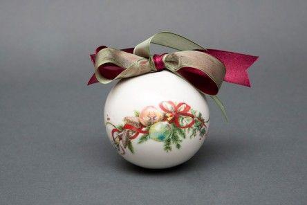 Elegante palla di Natale in finissima porcellana di Capodimonte finemente decorata con fantasia natalizia, raffinato fiocco amaranto e gancio (appendibile).             Dimensione cm. 9x9