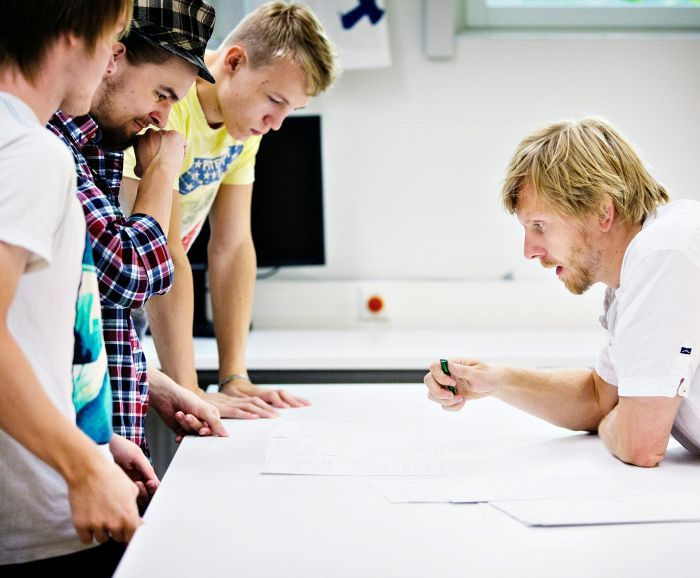 Pekka Peura käy tehtävää läpi Alexei Krammin (vas.), Markus Moilasen ja Ilkka Toivosen kanssa kolmannen luokan fysiikan tunnilla Martinlaakson lukiossa.