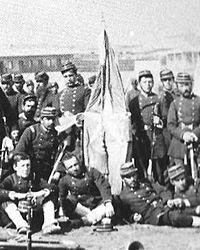 """Estandarte y escolta del Regimiento """"2º de Línea"""" de la Infantería del ejército de Chile, según una foto que la oficialidad se tomó en Antofagasta en 1879. Al momento de la batalla de Tarapacá el oficial portaestandarte era el subteniente Telésforo Barahona que murió en dicha acción de armas."""