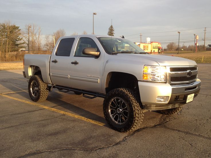nice lifted jacked silver colour Silverado Chev truck with  oversize tires
