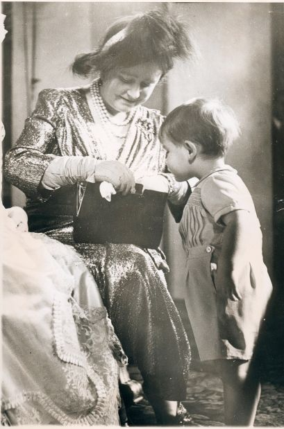 Oct. 21, 1950: Prince Charles looks on as his grandmother, the Queen Mother Elizabeth, looks in her purse at the christening of Charles' sister, Anne.