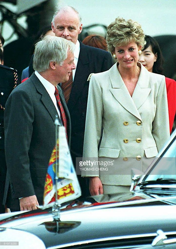 The Princess of Wales makes a face in the direction of the media covering her arrival in Hong Kong 21 April after Hong Kong Governor Chris Patten (L) points them out. Princess Diana is on a three-day working visit to the territory.