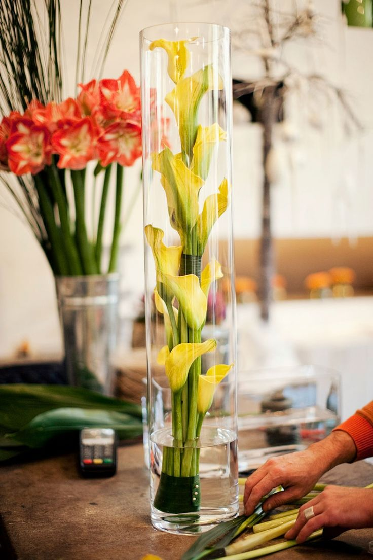 flower arrangements in glass vase on stand