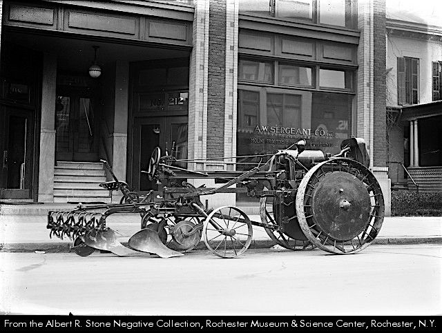 A. W. Sergeant Co., 212 East Avenue, dealers in Moline tractors and tractor implements. The rig has two large metal wheels in front, separated by a long drive train from the driver's seat and two smaller wheels. Various implements are attached to the back of the Moline Universal Tractor.