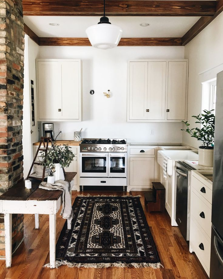 Adorable farmhouse kitchen with white cupboards and black rug