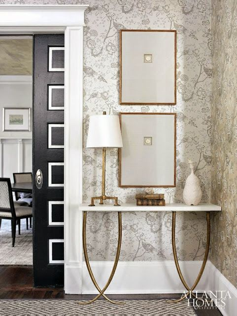 traditionally decorated white foyer black doors gold table wallpaper