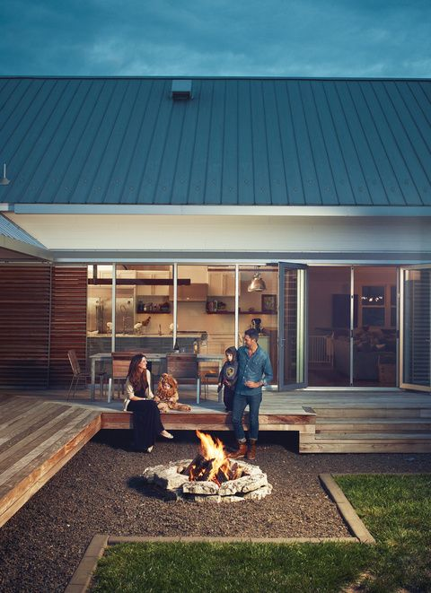Amazing modern farmhouse. The fire pit sits in a bed of stone immediately surrounding the deck - perfect maintenance solution and also ideal for keeping the grass and dirt out of the indoor/outdoor foot traffic.