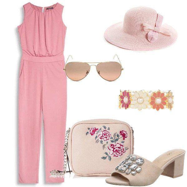 La splendida tuta rosa è abbinata alle mules color nude con pietre, la borsa a tracolla con fiori, il cappello di paglia con fiocco, gli occhiali aviatore rosati ed il bracciale con grandi fiori.