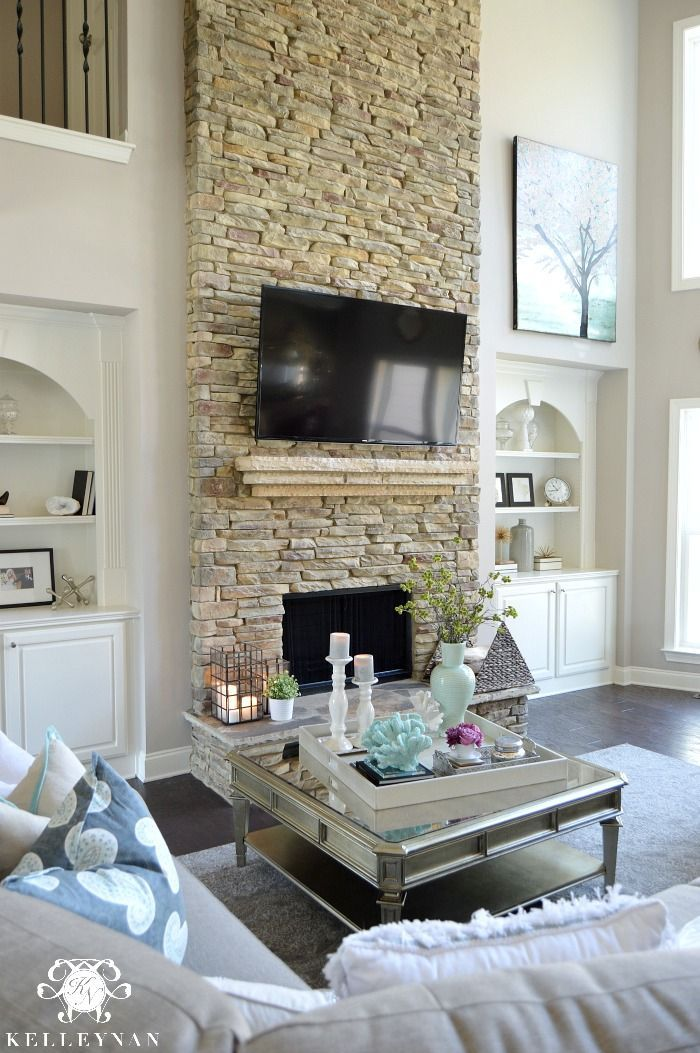 Kelley Nan: Cool Tone Spring Ready Living Room Tour- Two story neutral living room with two story windows in family room | Versatile Gray by Sherwin Williams | Dark hardwood floors in Nottaway Hickory Weathered Saddle | built-ins on either side of stacked stone fireplace in great room