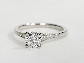 Ideal for any center diamond of your choice, this platinum engagement ring showcases a diamond accent along the shank and milgrain detailing.