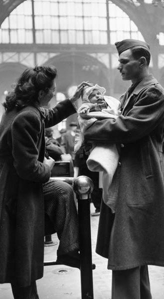 A soldier says goodbye to his wife and infant child in Pennsylvania Station before shipping out for service in World War II, New York City, 1943.